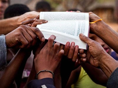 Group of hands holding a bible